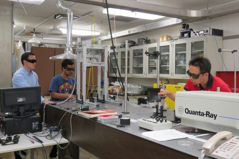 Professor Hongtao Ding (left), PhD students Avik Samanta (center) and Qinghua Wang (right) work on a nanosecond laser surface treatment system to conduct experiments in Ding's laser research lab in the IATL building. (Contributed)