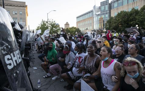 Protesters kneel in front of the police barricade during a protest outside of the Des Moines police station on Friday, May 29, 2020. An organized peaceful rally in honor of George Floyd and other victims of police brutality turned to violence following the event. Protesters threw water bottles at police while police sprayed tear gas and flares were thrown.