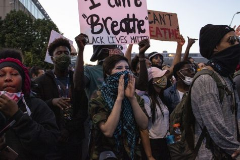 Chloe Bender (center) shouts at police stand in front of the police during a protest outside of the Des Moines police station on Friday, May 29, 2020. An organized peaceful rally in honor of George Floyd and other victims of police brutality turned to violence following the event. Protesters threw water bottles at police while police sprayed tear gas and flares were thrown. Bender was later tear gassed by police.