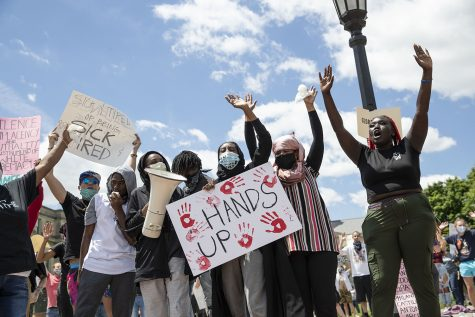 "Protesters raise their hands and chant ""Don't shoot"" during the Say Their Names rally on the Pentacrest on Saturday, May 30, 2020. Iowa City community members gathered to remember George Floyd, Ahmed Arbury, Yassin Mohamed and others. Money was collected during the event which went in donation to a vehicle procession carrying protesters going to Minneapolis. There were about five vehicles leaving directly following the rally."