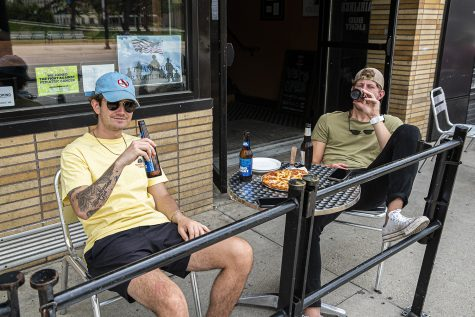 University of Iowa juniors Harrison Akienn and Michael Sehelbrop enjoy pizza and beer at the Airliner on Saturday, May 16th, 2020. The Airliner as well as various other local businesses are experiencing a surge in business due to commencement weekend and the state government lifting certain quarantine regulations.