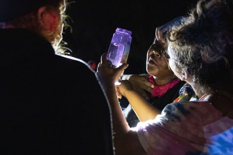 Crowd members help each other rinse their eyes with water after being pepper sprayed by police outside of Coral Ridge Mall in Coralville on Monday, June 1, 2020. Social media posts circulated Twitter and Facebook encouraging looters to break into the mall at 10:30 p.m. Police blocked the entrances and the crowd became violent as a man rushed an officer and police used pepper spray and flash bangs on the crowd. Several nearby businesses had property damage to windows and some protesters were handcuffed.
