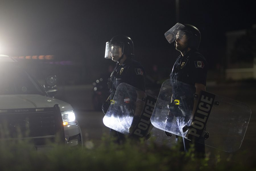 Officers stand with riot shields outside of the Coral Ridge Mall in Coralville on Monday, June 1, 2020. Social media posts circulated Twitter and Facebook encouraging looters to break into the mall at 10:30 p.m. Police blocked the entrances and the crowd became violent as a man rushed an officer and police used pepper spray and flash bangs on the crowd. Several nearby businesses had property damage to windows and some protesters were handcuffed.