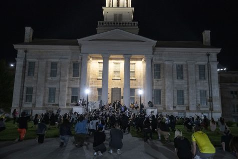 Protesters gather on the Pentacrest for a moment of silence during a protest in Iowa City on Monday, June 1, 2020. Protesters walk through downtown to the Johnson County Jail where they interacted peacefully with the police. Protesters then moved to the Iowa City Police Department where they smashed windows on a door.