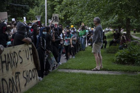 John Thomas, a member of the Iowa City City Council, stands outside his home and in front of a crowd of protesters on Saturday, June 13. The crowd was participating in a march to support the Black Lives Matter movement and congregated outside Thomas' house to ask what he is doing as a member of the city council to address their demands.