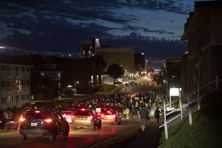 A crowd of protesters followed by a group of supporting vehicles travels west on Burlington Street towards downtown Iowa City during a march to support the Black Lives Matter movement and protest police brutality on Saturday, June 13.