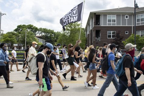 A protester walks with A Black Lives Matter flag on Saturday, June 20 on Burlington Street. The Iowa Freedom Riders hosted a celebration after the march to commemorate Juneteenth, the anniversary of when the last enslaved people were freed.
