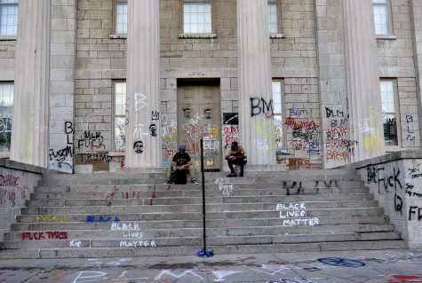 Protesters sit on the steps of the old Capitol while waiting for fellow protesters to gather during the Black Lives Matters march on Monday, June 23, 2020.
