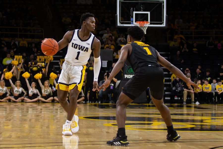 Iowa guard Joe Toussaint strategizes his next move to keep the ball away from Kennesaw State guard Terrell Burden during a basketball game against Kennesaw State University on Sunday, Dec. 29, 2019 at Carver Hawkeye Arena. The Hawkeyes defeated the Owls, 93-51.