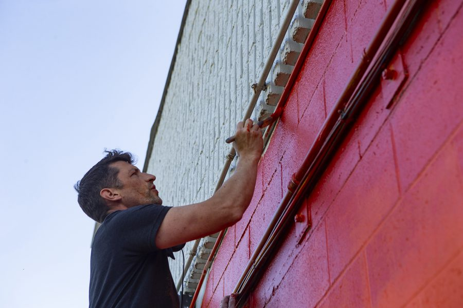 Artist Nick Meister paints a portion of a new mural on Saturday on Cross Park Ave. After several community painting days, Meister said he was excited to get his hands on the wall and do some painting himself. Although the artist debated community painting days at first, he said they ended up being a great way to bring everyone together.