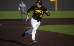 Iowa first baseman Peyton Williams watches where the ball is while racing to third base during a baseball game between the Iowa Hawkeyes and the Kansas Jayhawks on Tuesday, March 10, at Duane Banks Field. The Hawkeyes defeated the Jayhawks, 8-0. (Nichole Harris/The Daily Iowan)