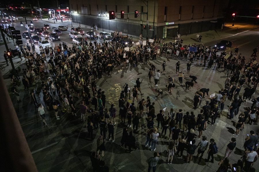 """A group of """"Black Live Matter Black Out Protest"""" participants spray paint the intersection of Linn and East Burlington St. on Tuesday, June 2, 2020. The group marched to various locations in Iowa City, including several city and county buildings. This marks the second night of protest in the community."""