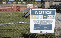 A sign for COVID-19 restrictions is posted outside the baseball field on Saturday, June 13 at West High School in Iowa City.