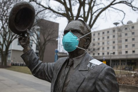 A mask sits on the Irving B. Weber statue in front of Van Allen on Thursday, March 12, 2020.