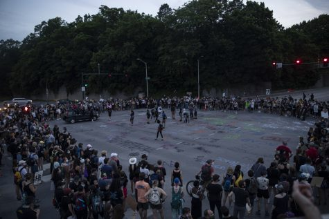 A crowd participating in a march to support the Black Lives Matter movement and protest police brutality stops at the intersection of Burlington Street and Riverside Drive to spray paint the intersection and chant in support of their cause.