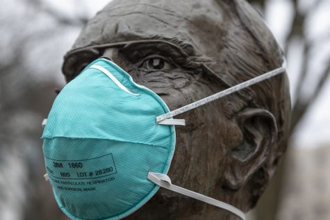 A mask sits on the Irving B. Weber statue in front of Van Allen on Thursday, March 12, 2020.   The US has seen a shortage of N95 surgical masks in the recent weeks due to coronavirus. The CDC currently recommends the use of facemarks be reserved for those who are sick or for those who are caring for the sick. (Katie Goodale/ The Daily Iowan)