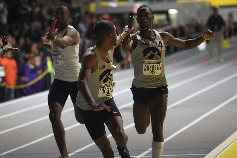 Antonio Woodward and Raymonte Dow make an exchange in the 4x400 meter relay during the Larry Wieczorek Invitational meet in Iowa City, Iowa; Saturday January 20, 2018. Their relay team finished second in the heat. (Paxton Corey/The Daily Iowan)
