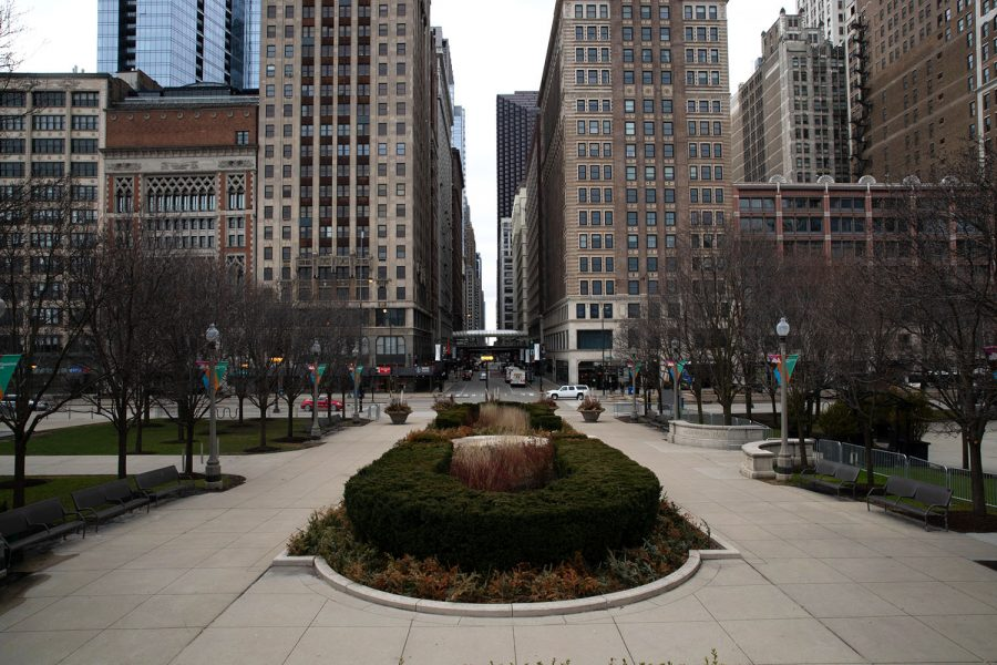 An+empty+plaza+in+Millennium+Park+sits+adjacent+to+the+sparsely+populated+intersection+of+Madison+Street+and+Michigan+Avenue+on+Tuesday%2C+March+21%2C+2020+in+Chicago%2C+Illinois.