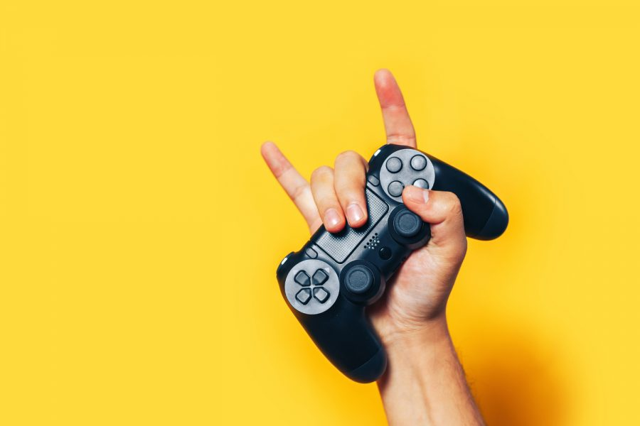 Man+hand+holding+black+gamepad+show+cool+symbol+on+yellow+background%2C+minimalism+concept.