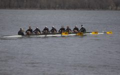 The Iowa varsity 8 crew looks to their supporters on the shore as they row back to the dock at the end of the first session of a women's rowing meet on Lake MacBride on Saturday April 13, 2019. Iowa won 3 out of 12 races with the varsity 8 crew winning both races for the day.