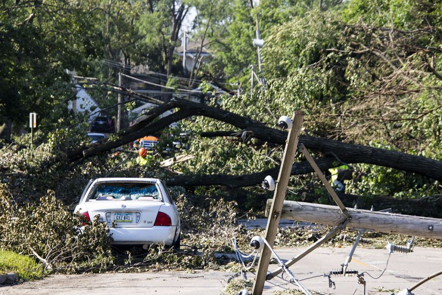 City+workers+work+to+remove+downed+trees+that+took+down+power+lines+and+landed+on+a+car+on+Linn+Blvd+SE.+As+seen+on+Friday%2C+Aug.+14%2C+2020.