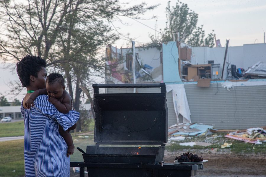 Sofia Saidi holds her child, Gabriel Elizabeth Bwira, while she grills dinner for her family on Thursday, August 14. She huddled with her three scared children in a corner of her apartment during the storm while her husband was at work. Like others in the apartment complex, she cooks every meal for her family like this.
