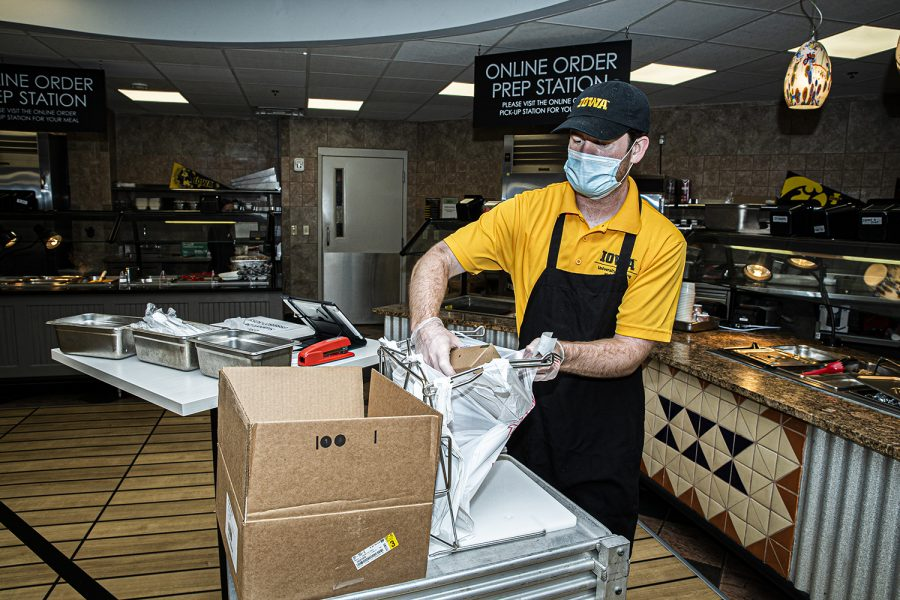 Burge Marketplace worker, Elijah Lyons prepares a takeout bag of dorm food on Monday, August 26th, 2020. Due to health and safety regulations as a means of preventing the spread of COVID-19, the dining hall process has been streamlined with an advanced registration process and a takeout meal process.