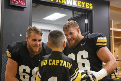 Offensive Linemen Levi and Landon Paulsen talk to Kid Captain Enzo Thongsoum in the Hawkeye football locker room at Kids Day at Kinnick on Saturday, August 10, 2019. Kids Day at Kinnick is an annual event for families to experience Iowa's football stadium, while watching preseason practice and honoring this year's Kid Captains.