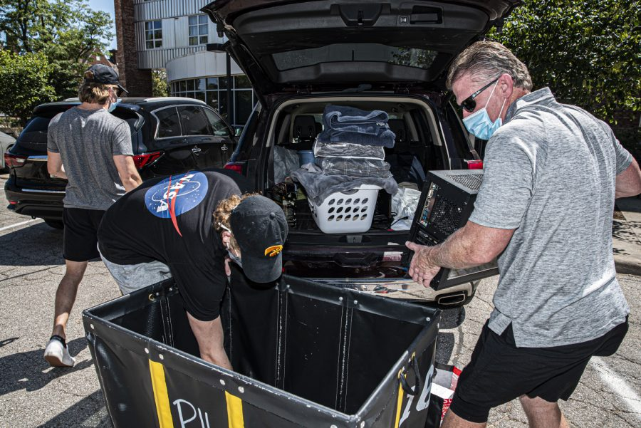 University of Iowa freshman Patrick Houston and his father, Tim Houston load a cart for moving into a dorm in Iowa City on Thursday, August 20th, 2020. The university is currently attempting to adjust their housing and orientation plans around the Coronavirus pandemic to maintain health and safety. (Tate Hildyard/ The Daily Iowan)