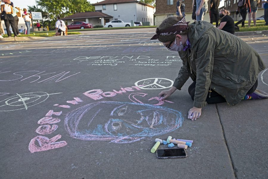 A young woman draws a portrait of George Floyd during chalk the walk outside of the Coralville Police Department on Monday, June 22, 2020.
