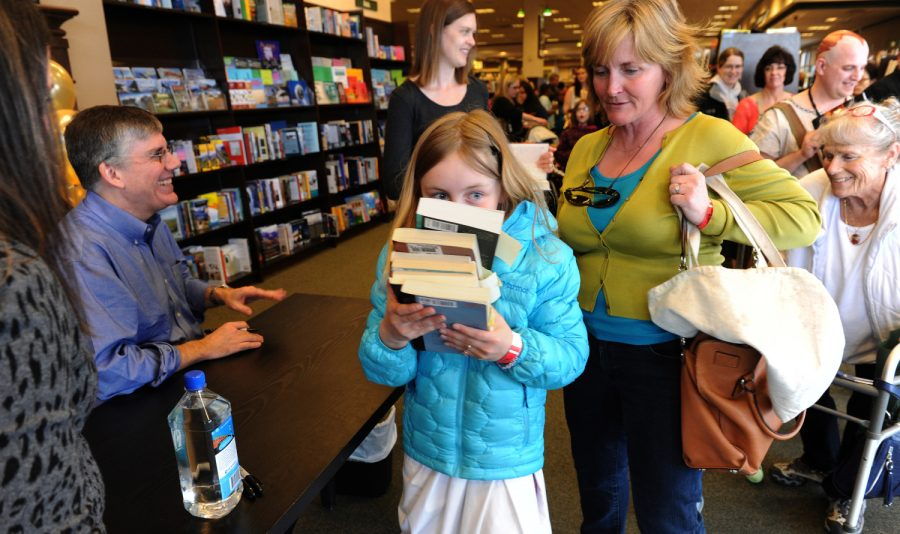 Piper Sage carries off an armful of Rick Riordan books with her mom, Charla Sterne. The author, left, signed his new book the