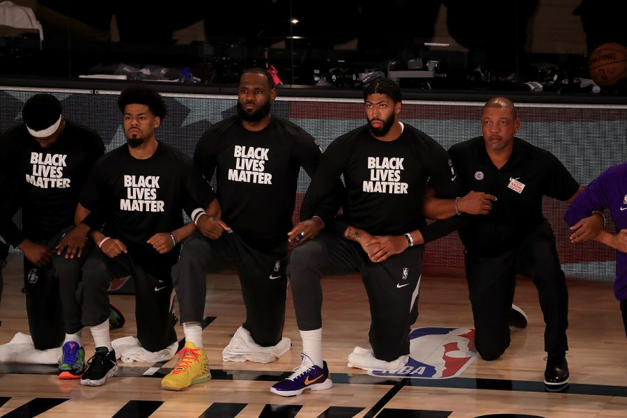The Los Angeles Lakers, including LeBron James and Anthony Davis, wear Black Lives Matter shirts while kneeling during the national anthem prior to a game against the Los Angeles Clippers and head coach Doc Rivers, right, at The Arena at ESPN Wide World Of Sports Complex in Lake Buena Vista, Florida, on Friday, July 30, 2020.