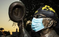 A statue clad with swim cap, goggles, and face mask depicting former historian and University of Iowa athlete Irving Weber stands near the Van Allen building on Sunday, August 23, 2020, two days after the decision by the University of Iowa to cut the men's and women's swim and dive program along with men's gymnastics and men's tennis. While known for his work as a historian in Iowa City, Weber also maintains importance as the first All-American swimmer at Iowa, gaining the status in 1922 in the 150 yard backstroke. (Ryan Adams/The Daily Iowan)