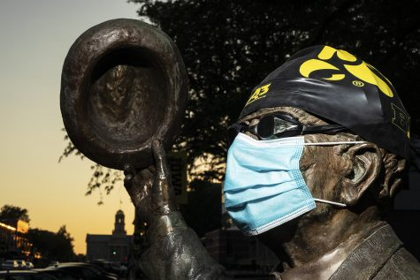 A statue clad with swim cap, goggles, and face mask depicting former historian and University of Iowa athlete Irving Weber stands near the Van Allen building on Sunday, August 23, 2020, two days after the decision by the University of Iowa to cut the men