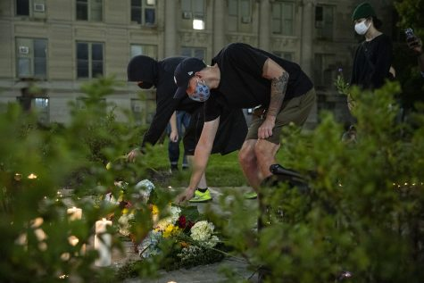 Protesters lay flowers down on a memorial built for Makeda Scott during a Black Lives Matter protest organized by the Iowa Freedom Riders on Saturday, Aug. 29, 2020. This protest, a part of a four day protest streak, included a memorial for UI student Makeda Scott. Mourners left flowers and candles in front of the Old Capitol Building.