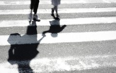 Blurry shadow and silhouette of mother and child at zebra crossing.