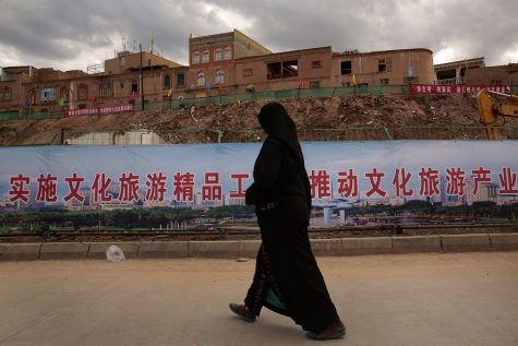 An Uyghur woman walks along an area of reconstruction in Kashgar, China. Many homes in the old urban district of Kashgar are being reconstructed, and many have been raised to build a new park.