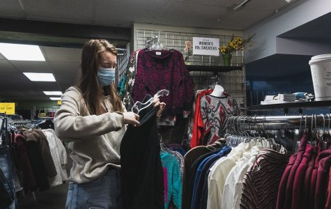Adriana Swiatek putting a shirt on a hangar while she's working at Ragstock clothing store on Thursday Sept. 10, 2020. Swiatek said her perspective on how people view COVID-19 has been changed by her interactions with customers.