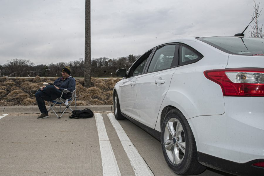University of Iowa graduate student Philip Zaborowski does homework in the parking lot of Hancher Auditorium on Tuesday, April 2, 2020. As a result of COVID-19 creating a sudden influx of at-home work, the university attempted to aid in the congestion of internet traffic by installing free Wi-Fi in the Hancher parking lot.