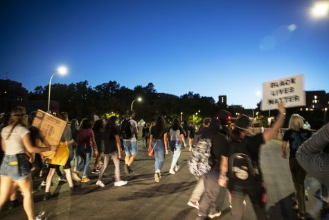 Protesters walk down Burlington Street during a Black Lives Matter protest organized by the Iowa Freedom Riders on Saturday, Aug. 29, 2020. This protest, a part of a four day protest streak, included a memorial for UI student Makeda Scott. Mourners left flowers and candles in front of the Old Capitol Building.