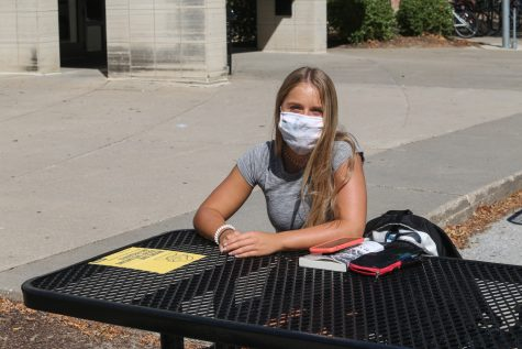 Taylor Ford poses for a portrait on Thursday, Sept. 3 in front of Burge Residence Hall in Iowa City. Ford was released from a quarantine floor in Burge that morning and was taking advantage of her release by reading outside in the afternoon.