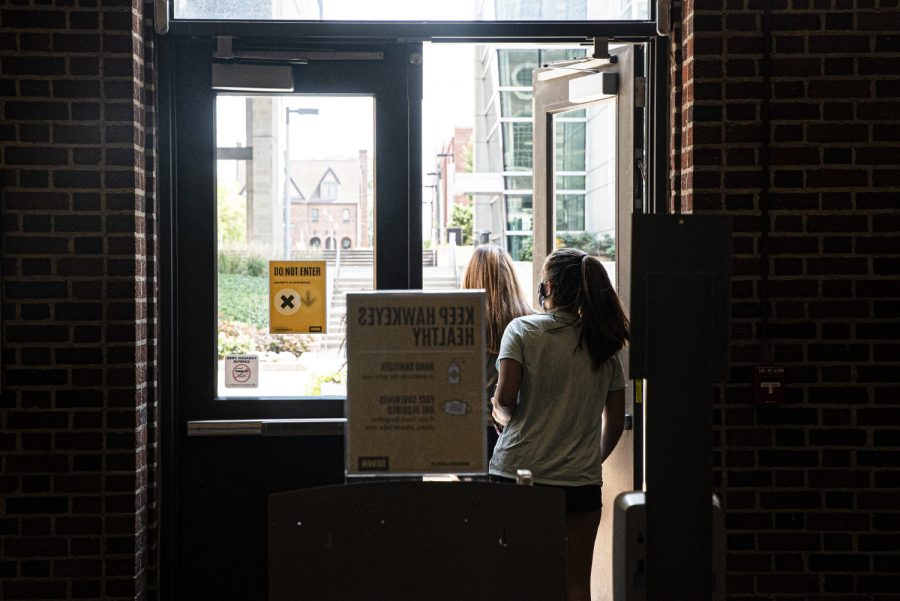 A pair of University of Iowa students leave the nearly deserted Chemistry Building on the first day of the new semester on Monday, August 24th, 2020. Despite the pandemic, campus remains open and some classes are still being held in person.