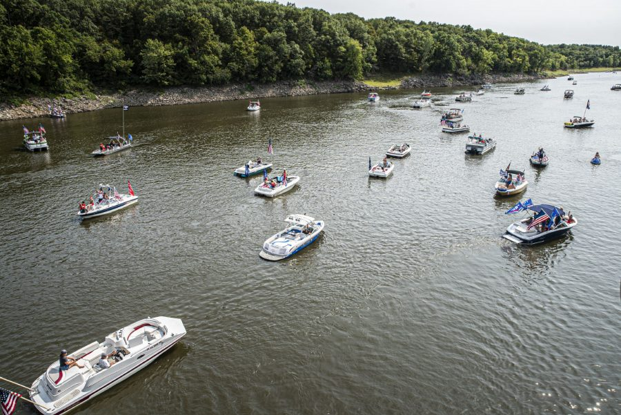 A group of boats decorated in Donald Trump paraphernalia pass under a bridge on Monday, Sept. 7, 2020. For Labor day, a group of local Trump supporters decided to drive their boats around Coralville Lake to celebrate and to show support for President Trump. (Tate Hildyard/ The Daily Iowan)