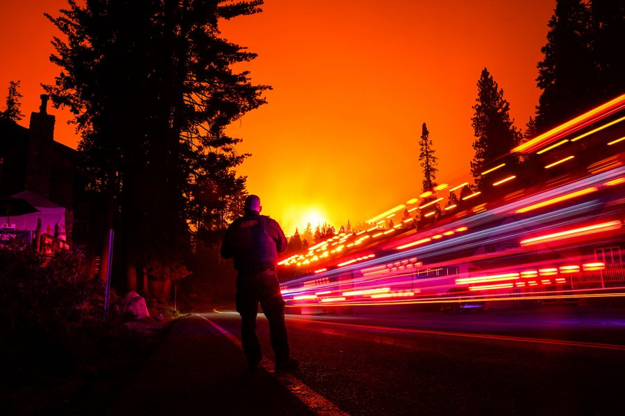 A+vehicle+streaks+by+in+a+long+exposure+as+Fresno+County+Sheriff+Deputy+Jeffery+Shipman+stands+along+CA-168+as+the+Creek+Fire+creeps+closer+to+town+on+Sunday%2C+Sept.+6%2C+2020+in+Shaver+Lake%2C+California.+%28Kent+Nishimura%2FLos+Angeles+Times%2FTNS%29