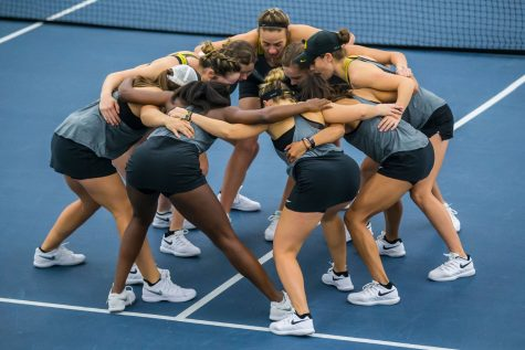 Iowa players huddle before doubles play during a women