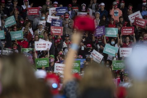 Attendees hold signs on the bleachers during a Trump campaign rally on Wednesday, Oct. 14, 2020 at the Des Moines International Airport. Thousands of people showed up to hear President Donald Trump speak about his campaign and support Iowa republicans for the upcoming election.