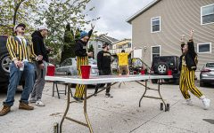 "A group of University of Iowa seniors play a game of dye outside while tailgating on Saturday, October 24th, 2020. Despite it being an away game, a handful of Iowa City residents still decided to celebrate with their own, small scale tailgates. ""Yeah there's a lot going on right now, but we all live together anyway so this is safe and for a lot of us, this is our last first tailgate of the season so we figured we had to do something."
