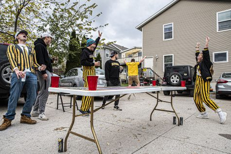 "A group of University of Iowa seniors play a game of dye outside while tailgating on Saturday, October 24th, 2020. Despite it being an away game, a handful of Iowa City residents still decided to celebrate with their own, small scale tailgates. ""Yeah there's a lot going on right now, but we all live together anyway so this is safe and for a lot of us, this is our last first tailgate of the season so we figured we had to do something."""