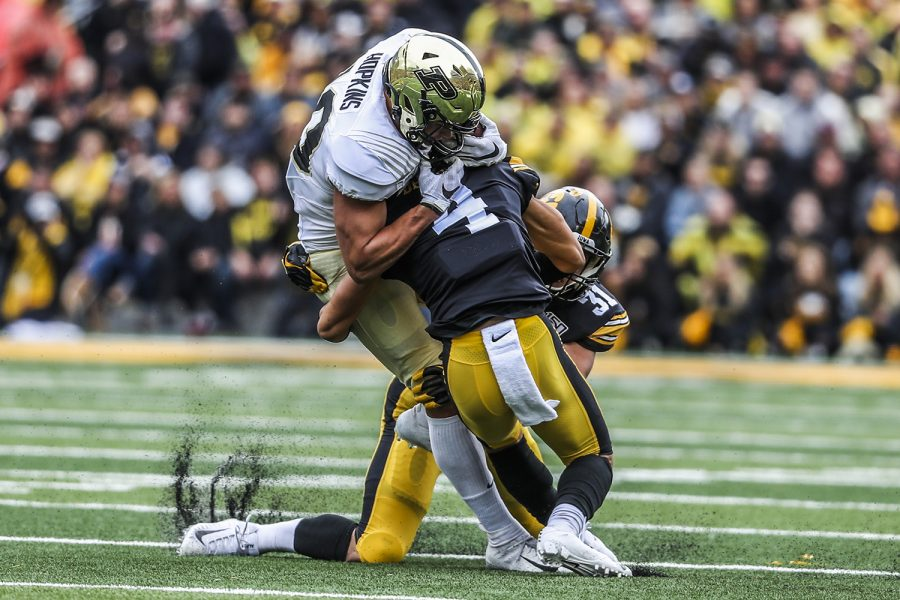 Iowa defensive back Dane Belton tackles Purdue tight end Brycen Hopkins during the Iowa football game against Purdue at Kinnick Stadium on Saturday, Oct. 19, 2019. The Hawkeyes defeated the Boilermakers 26-20.