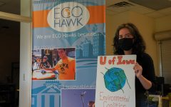 Emily Manders holds up a University of Iowa Environmental Coalition sign in the University of Iowa Office of Sustainability and the Environment at Jessup Hall, Iowa City, IA on Wednesday Oct. 7, 2020. Manders, co-president of the UI Environmental Coalition, believes the Climate Change Clock ignores lower income communities and people of color who have already seen or felt the impact of climate change.
